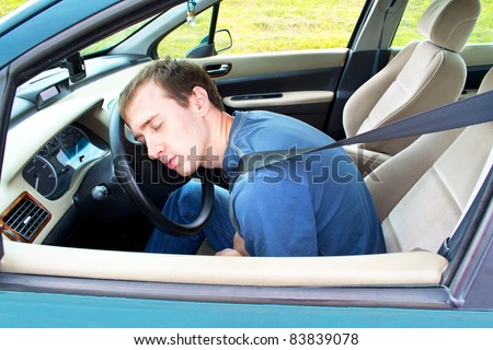 man sleeps in a car - stock photo