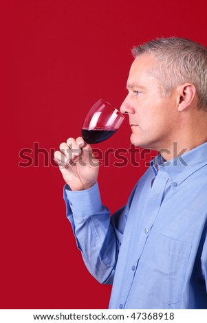 Man smelling a glass of red wine to check it's aroma - stock photo