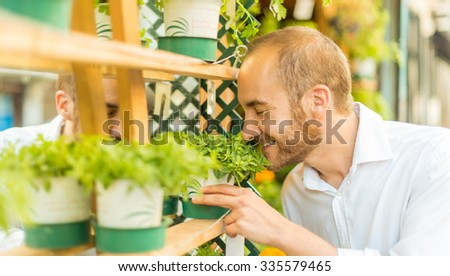 Man smelling the aroma of fresh plants in a shop - stock photo