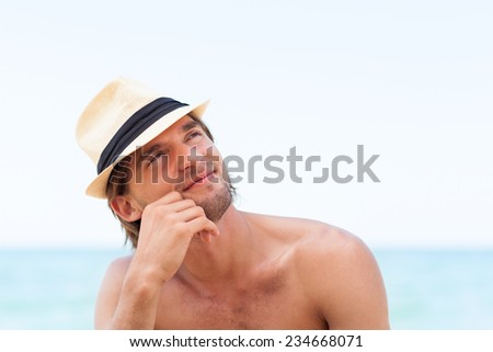 man smile on beach Handsome young male think look up to empty copy space, dream hold hand finger on chin wear hat - stock photo