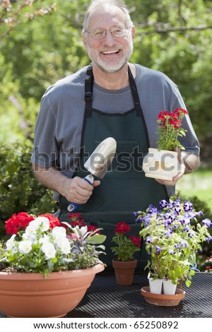 Man smiles at the camera while gardening with potted plants outdoors. - stock photo