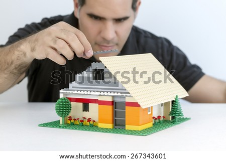 Man smiles while building a house with small parts in plastic - stock photo