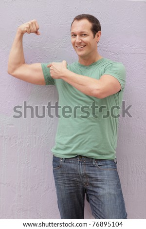 Man smiling and flexing his arm muscles - stock photo