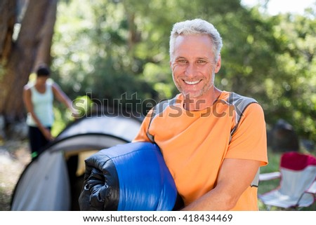 Man smiling and holding a sleeping bag on a camp site - stock photo