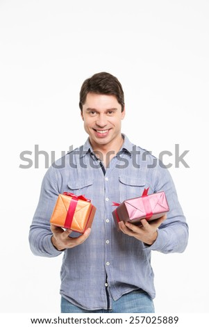 Man smiling and holding gifts on the hands on a white background - stock photo
