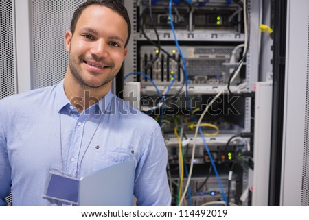 Man smiling and standing in front of data servers - stock photo