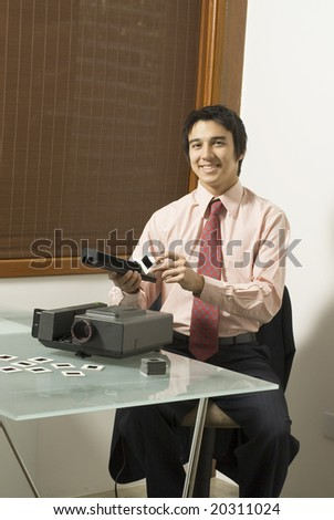 Man smiling as he looks at a slide next to a projector. Vertically framed photo. - stock photo