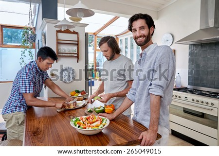 Man smiling at camera while at friends party in kitchen - stock photo