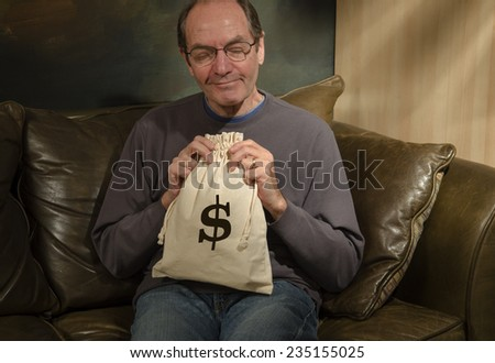man smiling holding burlap bag with dollar sign - stock photo