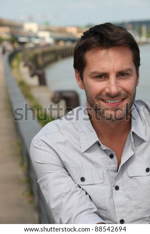 Man smiling next to the river.