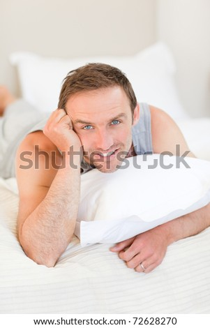 Man smiling on his bed