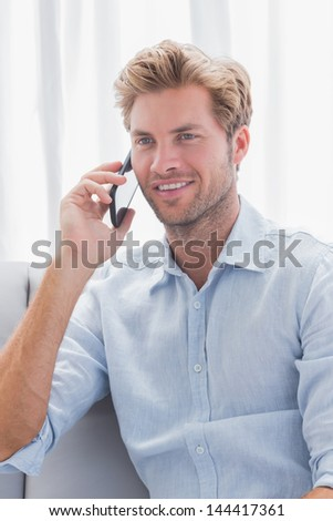 Man smiling while he is having a phone conversation on the couch - stock photo