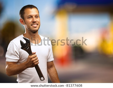 man smiling with a wrench against a oil station
