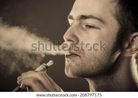 Man smokes electronic cigarette on dark background. - stock photo