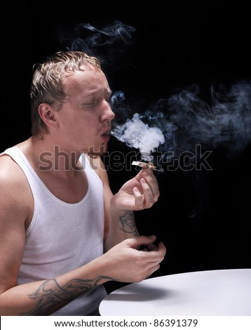 Man smokes in the dark - stock photo