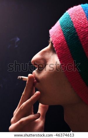 Man smokes marijuana on black background - stock photo