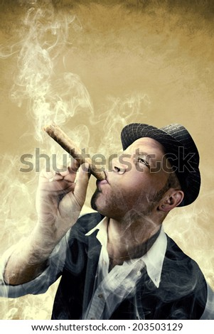 man smoking a big cigar surrounded by smoke - stock photo