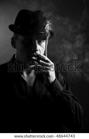 Man smoking a cigar. Dark background. - stock photo