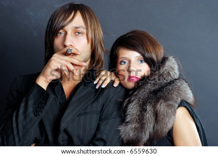 Man smoking a cigar while a gorgeous woman leans on his shoulder.