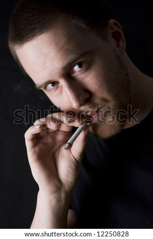 man smoking a cigarette against black background