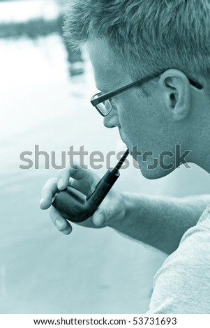 man smoking a pipe, river on background - stock photo