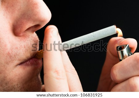Man smoking against a black background - stock photo