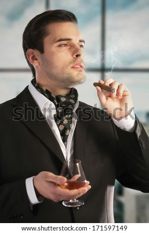 Man smoking cigar and drinking cognac - stock photo