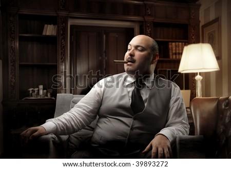 man smoking cigar in a luxury office - stock photo