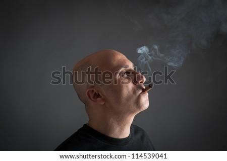 Man smoking cigar portrait on dark background. - stock photo