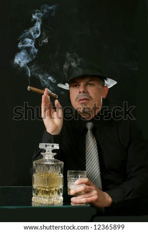 man smoking cigar with a glass of alcohol