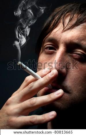 Man smoking cigarette over black background, low key light image - stock photo