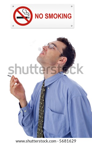 Man smoking cigarette under a NO SMOKING plate