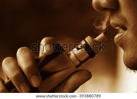 man smoking e-cigarette with the smoke on the side - stock photo