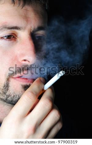 Man smoking in dark - stock photo