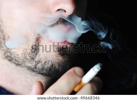 Man smoking in dark with visible smoke - stock photo