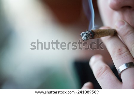 Man smoking marijuana cigarette soft drug in Amsterdam, Netherlands - stock photo