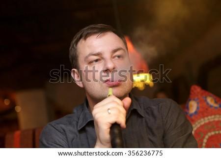 Man smoking nargile in the arabic cafe - stock photo