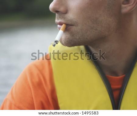 man smoking outdoors - stock photo