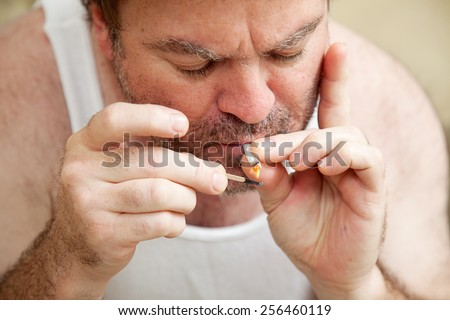 Man smoking pot,  lighting a joint with a match.   - stock photo
