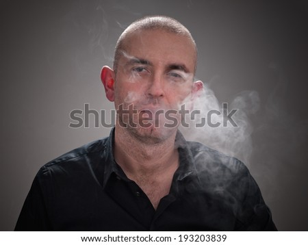 Man smoking with smoke in his face isolated on grey background
