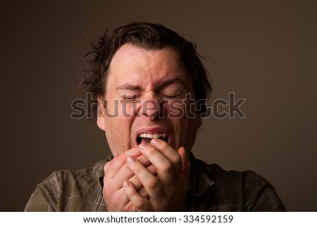 Man sneezing due to having a cold - stock photo