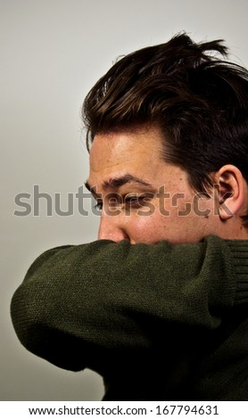 Man sneezing into his arm - stock photo