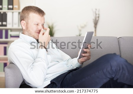 Man snickering to himself as he reads his tablet computer holding his hand in front of his face as he lies back comfortably on a sofa at home
