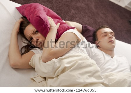 Man snoring on the bed and her wife can't sleep - stock photo