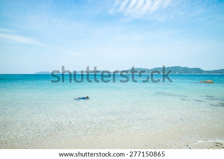 Man snorkeling in crystal clear waters on perfect paradise beach full of white sand and turquoise water during Summer