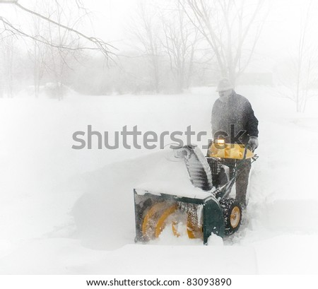 Man snow blowing in a New England blizzard - stock photo