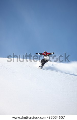 Man snowboarding down hill - stock photo
