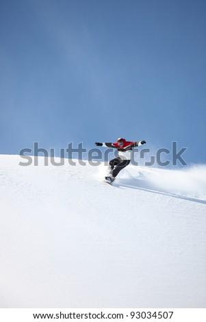 Man snowboarding down hill - stock photo