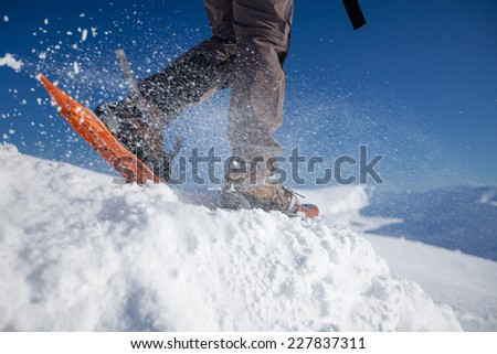 Man snowshoeing in wintertime outdoor - stock photo