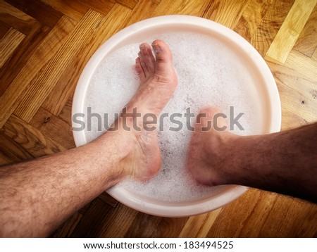 Man soaking his feet in a washbowl. - stock photo